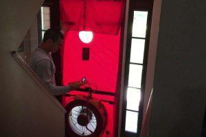 A technician performing a blower door test in Warwick, RI